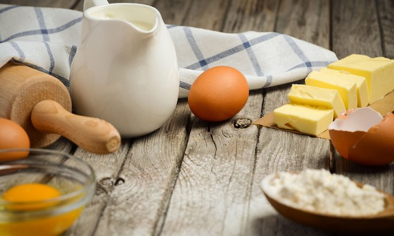 Ingredients for baking - milk, butter, eggs and flour. Rustic ba